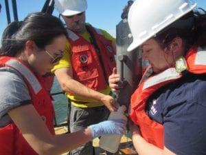 Yuan Liu fills a water sampling bottle on a boat at sea.